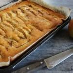 een appelcake in een platte ovenschaal gebakken en, gevuld met losse schijfjes appel