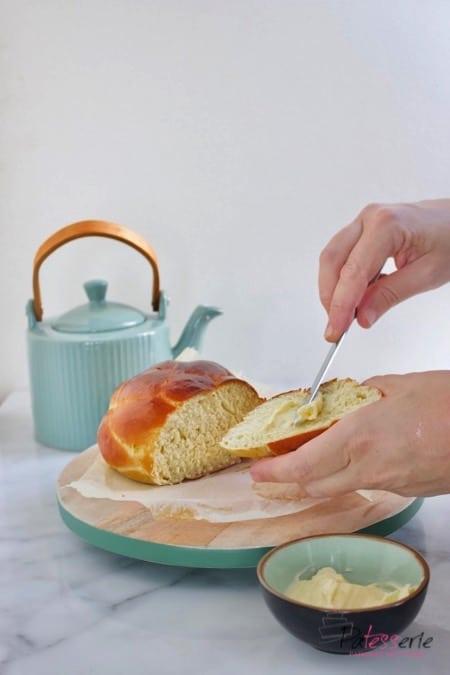 Een luchtig gevlochten aardappelbrood, wat besmeerd wordt met boter, op een snijplank met een theepot ernaast.