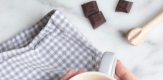 Een grote mok met de lekkerste chocolademelk gemaakt met pure chocolade en warme melk. Blokjes single origin chocolade ernaast om aan te geven dat kwaliteitschocolade extra smaak geeft