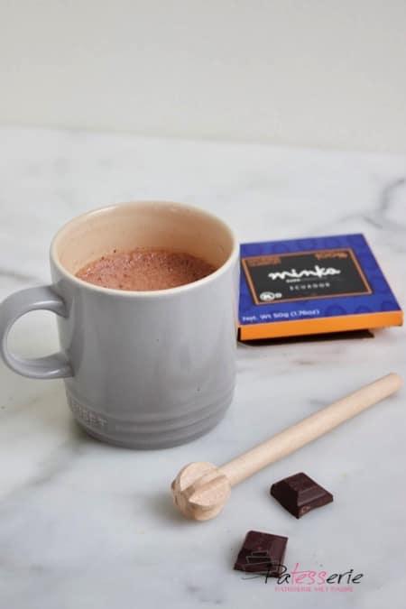 Een mok met de lekkerste chocolademelk gemaakt met 100% pure chocolade en gemixt met een traditionele houten mixer