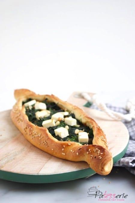 Turkse pide, een ovaal vormig open brood gevuld met spinazie, feta en pijnboompitten