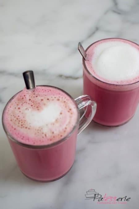 Twee mokken met Red Velvet Latte. Koffie met roze melk en een klein laagje melkschuim. Gemaakt met bietensap voor de roze kleur en chocolade voor de red velvet smaak