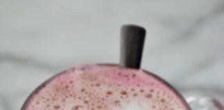Een mok met Red Velvet Latte. Koffie met roze melk en een klein laagje melkschuim. Gemaakt met bietensap voor de roze kleur en chocolade voor de red velvet smaak