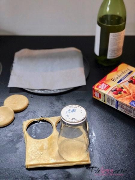 Arnhemse meisjes koekjes maken van bladerdeeg waarbij een glas als uitsteker wordt gebruikt, de bodem van een springvorm als bakplaat en een fles wijn als deegroller