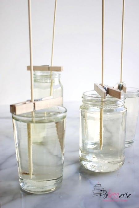 potjes met suikerwater waar een sateprikker inhangt, vastgezet met een knijper om zo kandijsuiker op een stokje te maken