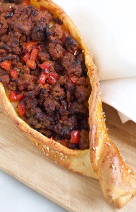 pide met pittige gehaktvulling en paprika op een houten plank
