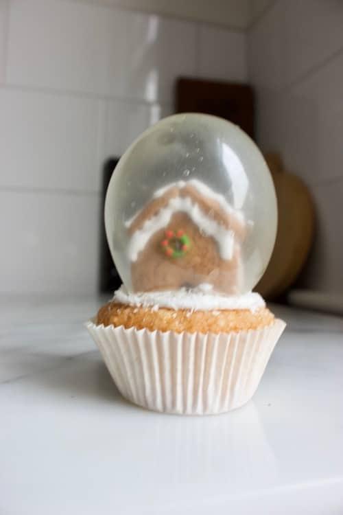 sneeuwbol cupcake met gelatine ballonnen en peperkoeken huisje erin