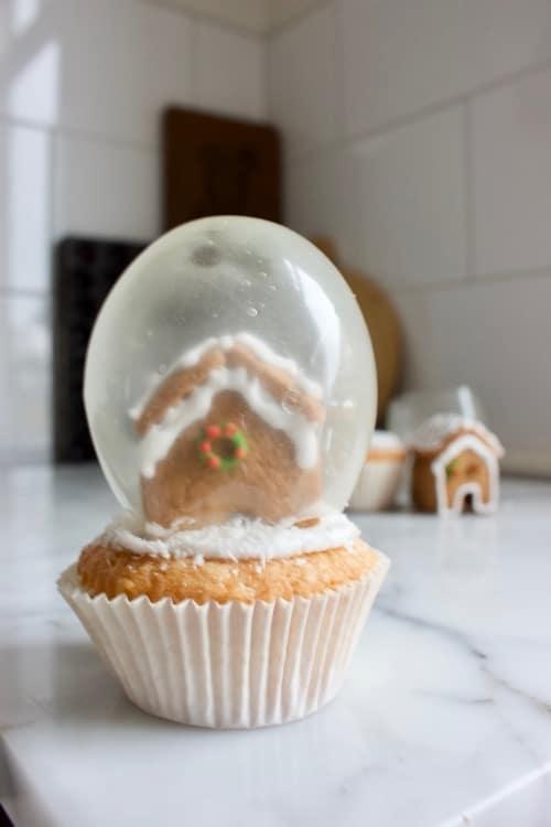 sneeuwbol cupcake met gelatine ballonnen en peperkoeken huisjes
