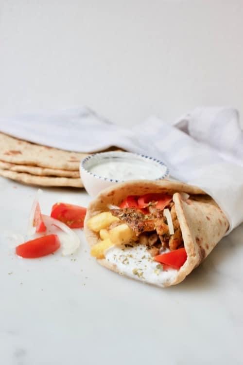 gevuld grieks pitabrood geserveerd met tomaat, uit en tzatziki
