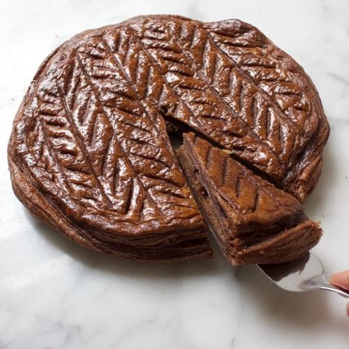 Driekoningentaart met chocolade waar een taartpunt uitgesneden wordt