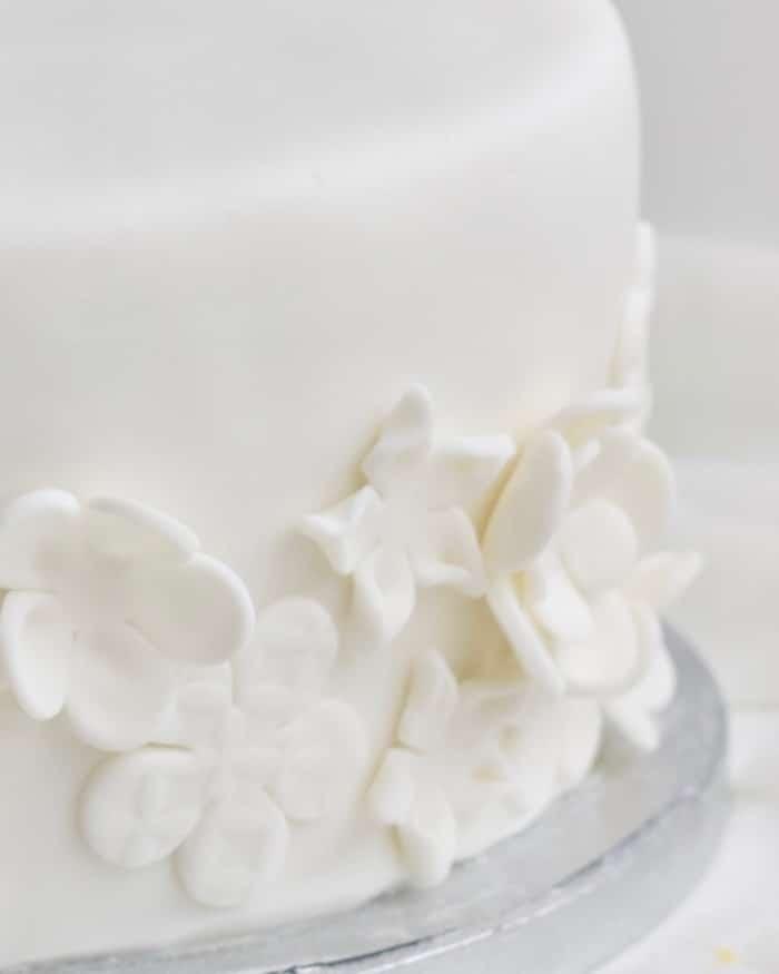 Detail van een een witte fondant taart met fondant bloemen