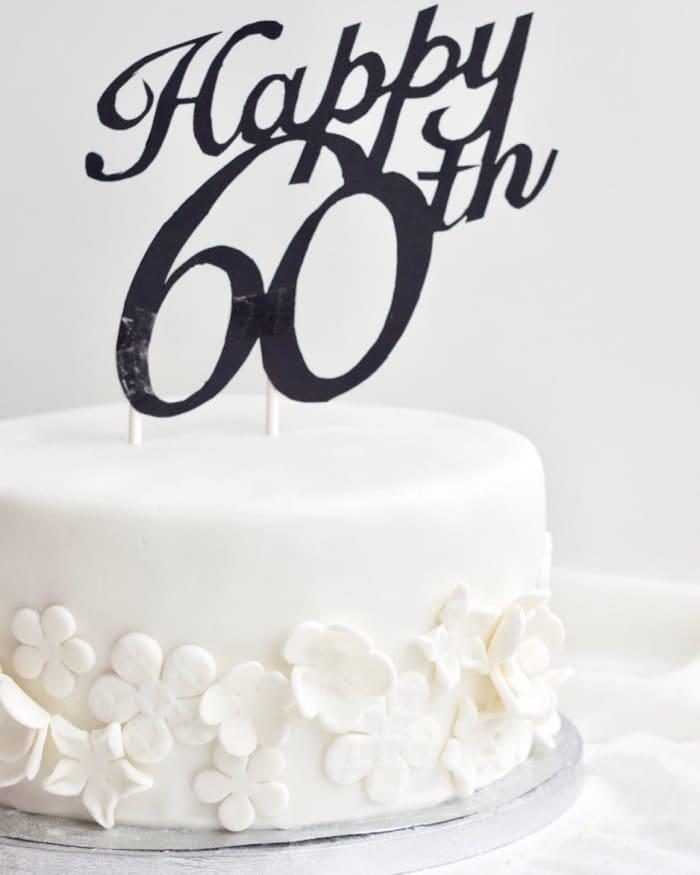 Voorbeeld van een fondant taart maken, wit met bloemen en taarttopper 60 jaar