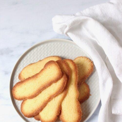 kattentongen koekjes op een schotel met wit servet ernaast