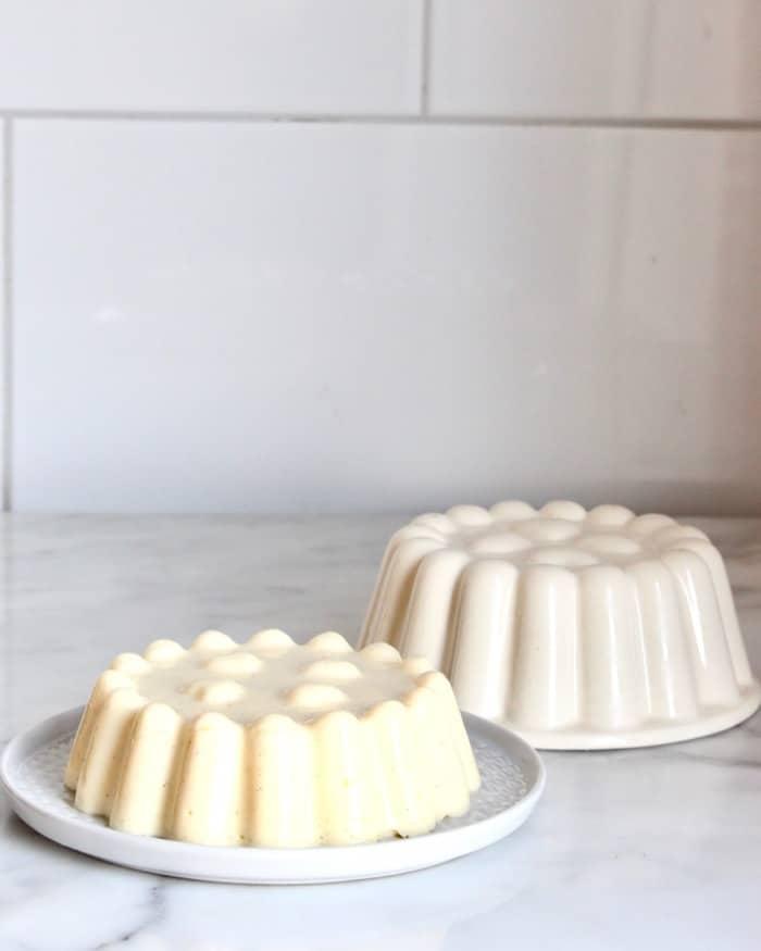 vanille pudding op een schotel en een ouderwetse witte puddingvorm ernaast