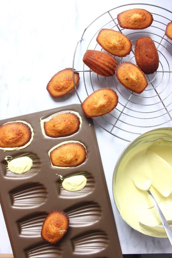 madeleines met een chocolade laagje in het bakblik en op het rooster